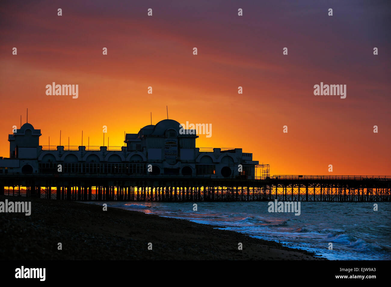 Red sky in the morning as the sun rises behind Southsea Pier at Portsmouth in Hampshire - Stock Image