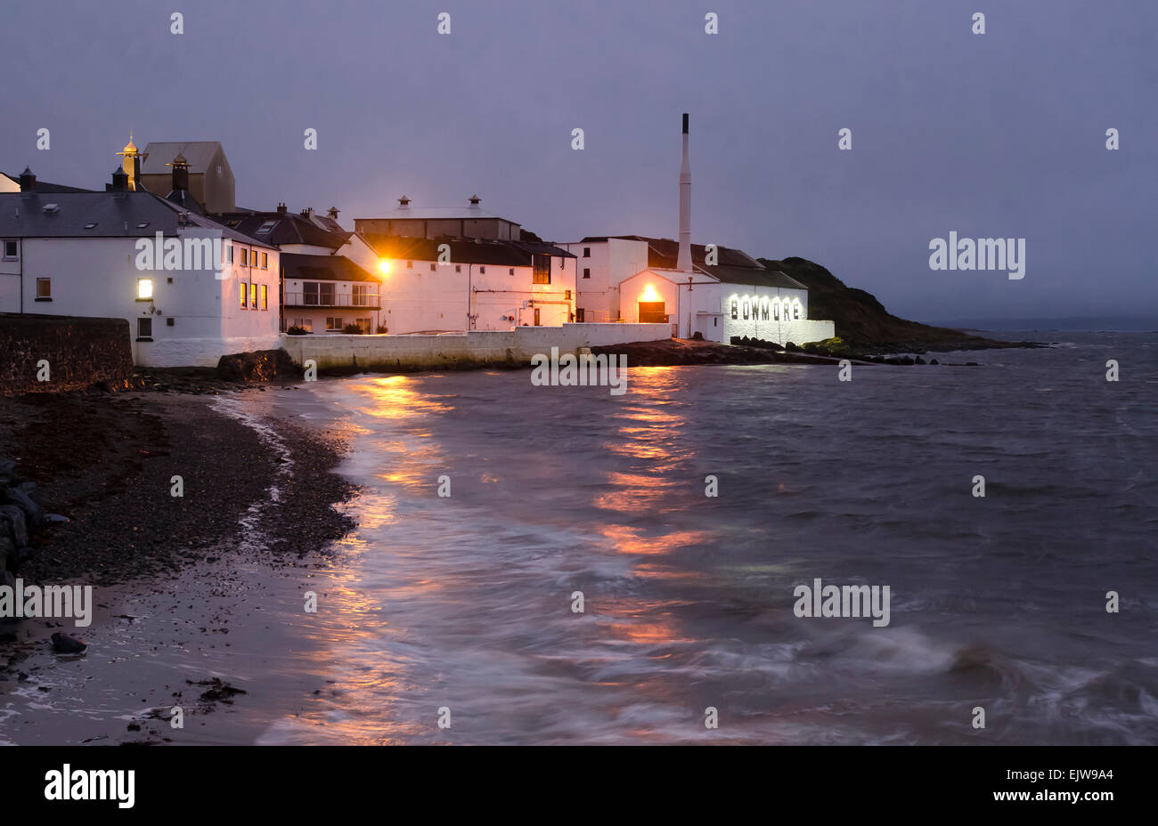 bowmore distillery at dusk with shoreline and lapping seawater - Stock Image