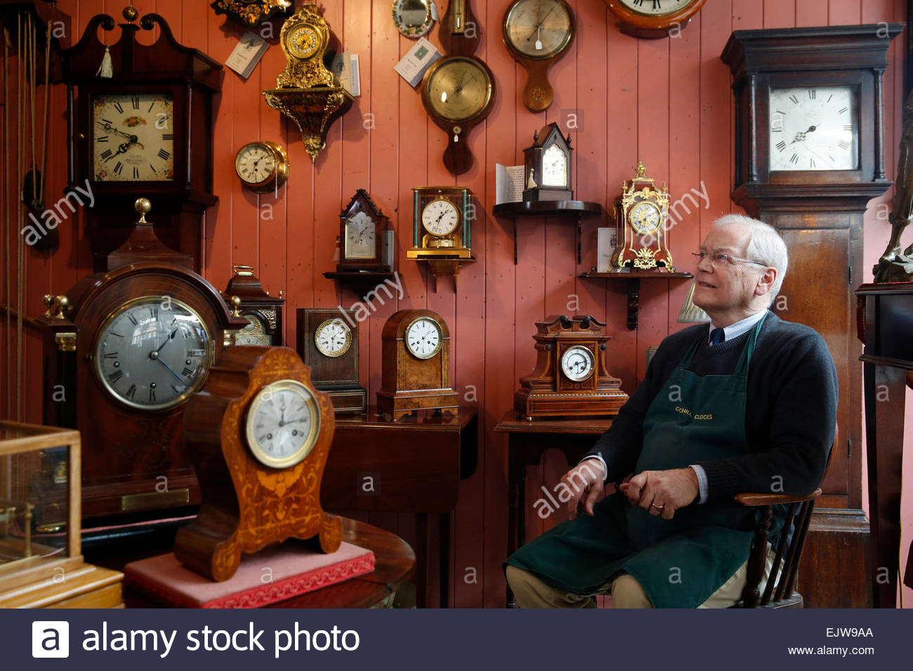 Antique clock restorer William Tyrrell sits among his clocks at 'Churchill Clocks' in Midhurst, West Sussex - Stock Image