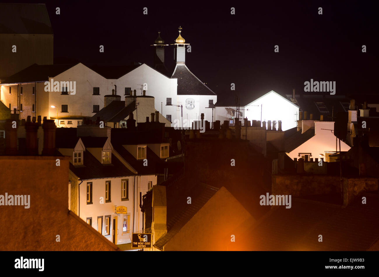 bowmore with distillery and street lights at dusk - Stock Image