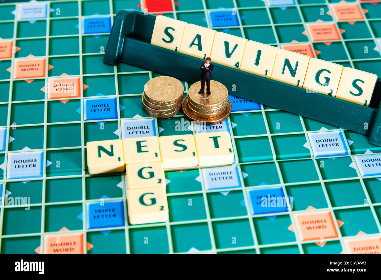 nest egg savings money pound coins pension save rainy day words fund using scrabble tiles to illustrate spelling - Stock Image