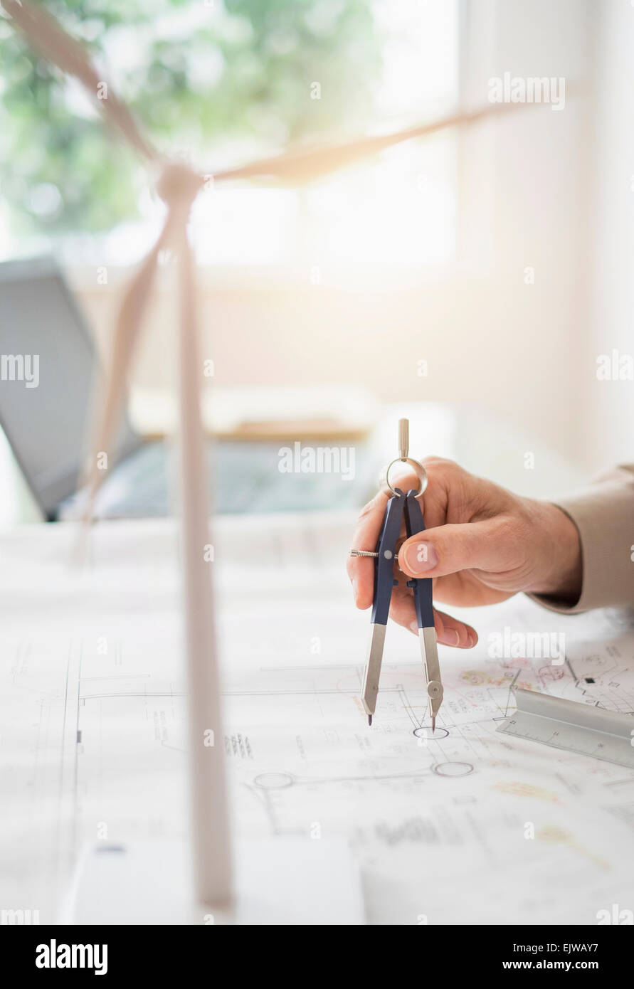 Close up of man's hands using compass while drawing plans - Stock Image