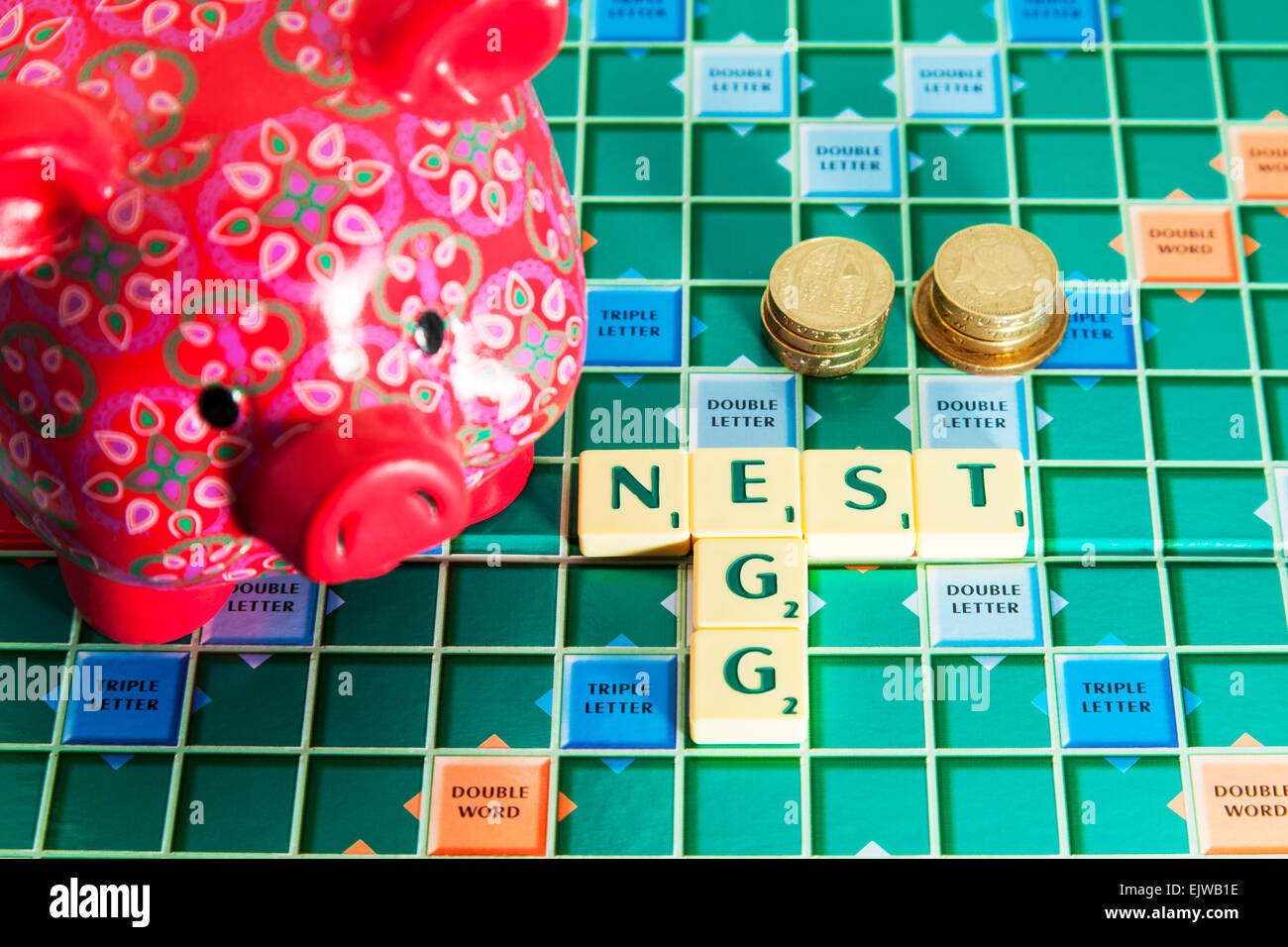 piggy bank nest egg savings money pension future save cash words using scrabble tiles to spell out - Stock Image