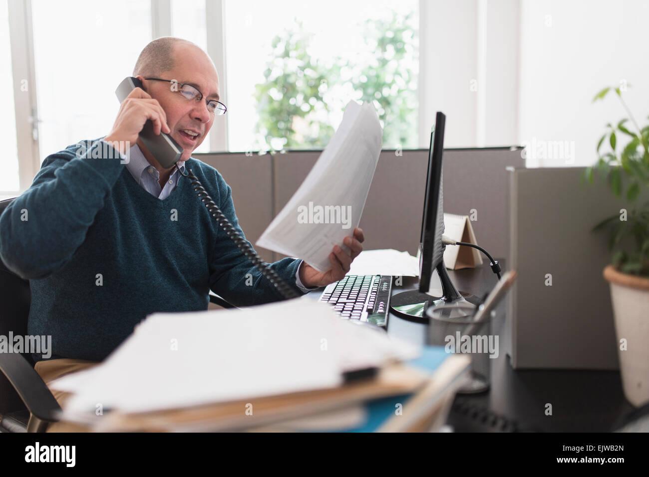 Mature businessman using landline phone in office - Stock Image