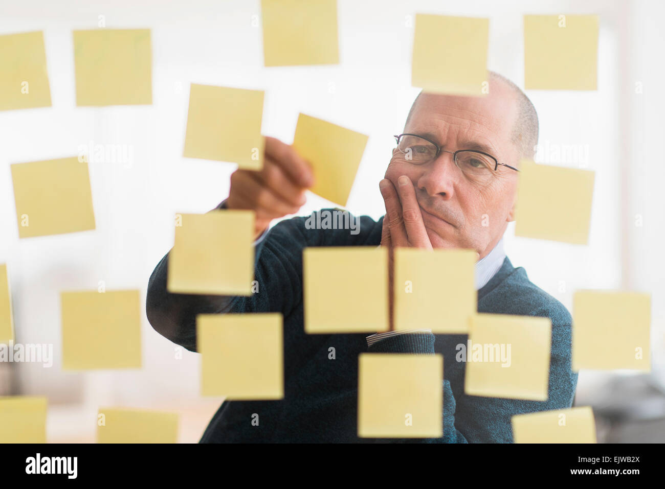 Businessman arranging adhesive notes on glass wall Stock Photo ...