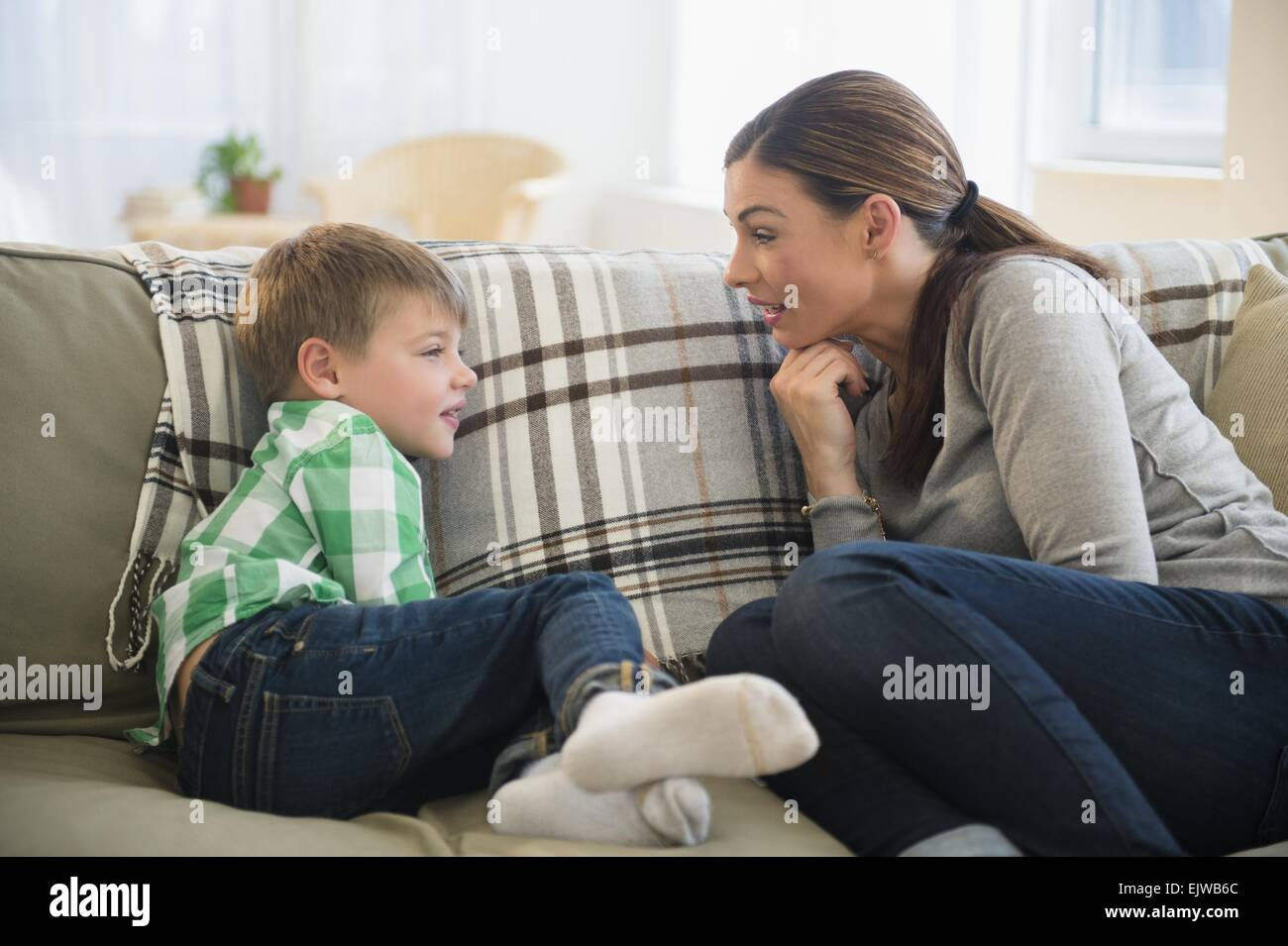 Mother and son (6-7) sitting on sofa - Stock Image