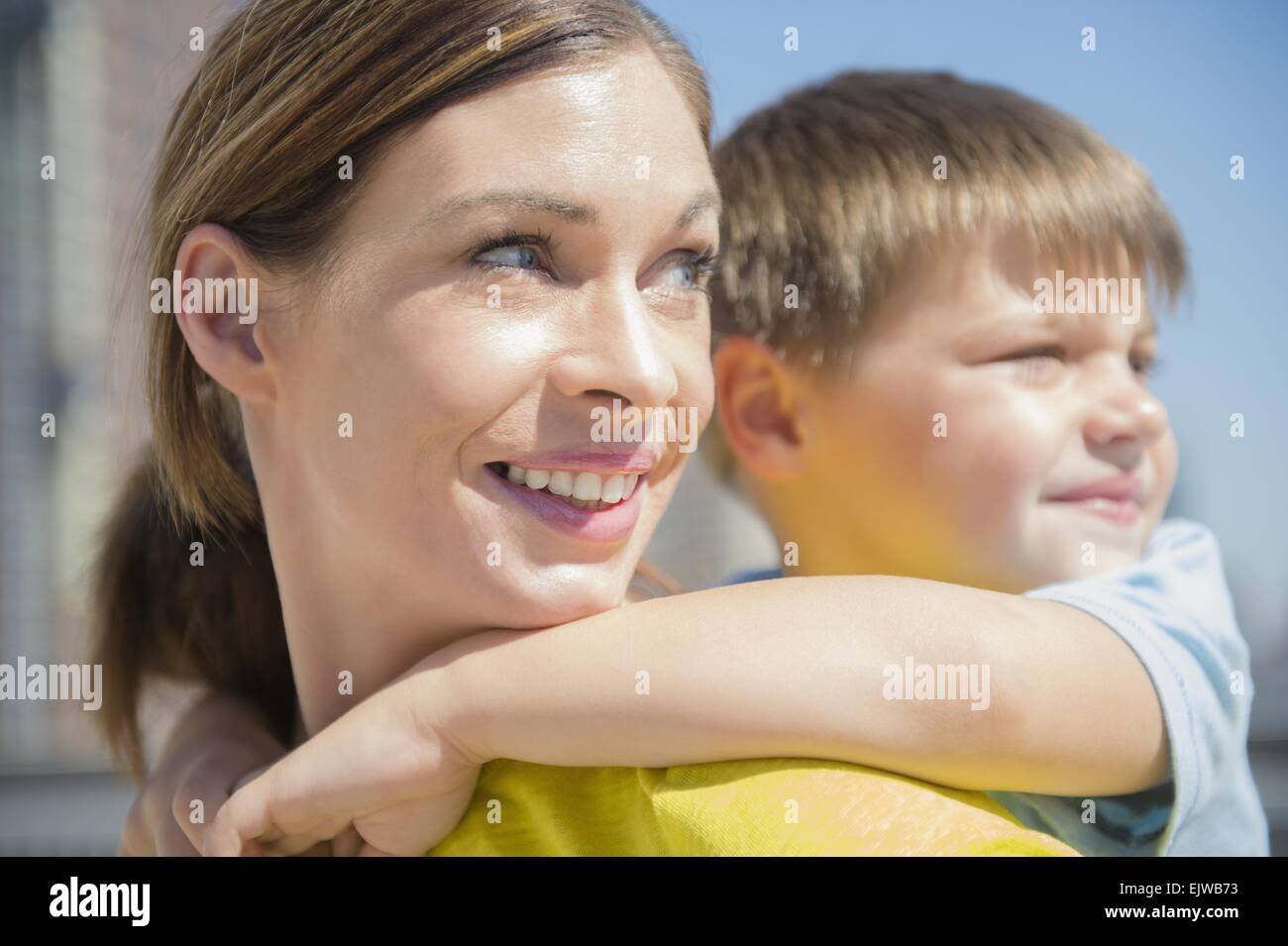 Mother giving her son (6-7) piggyback ride Stock Photo