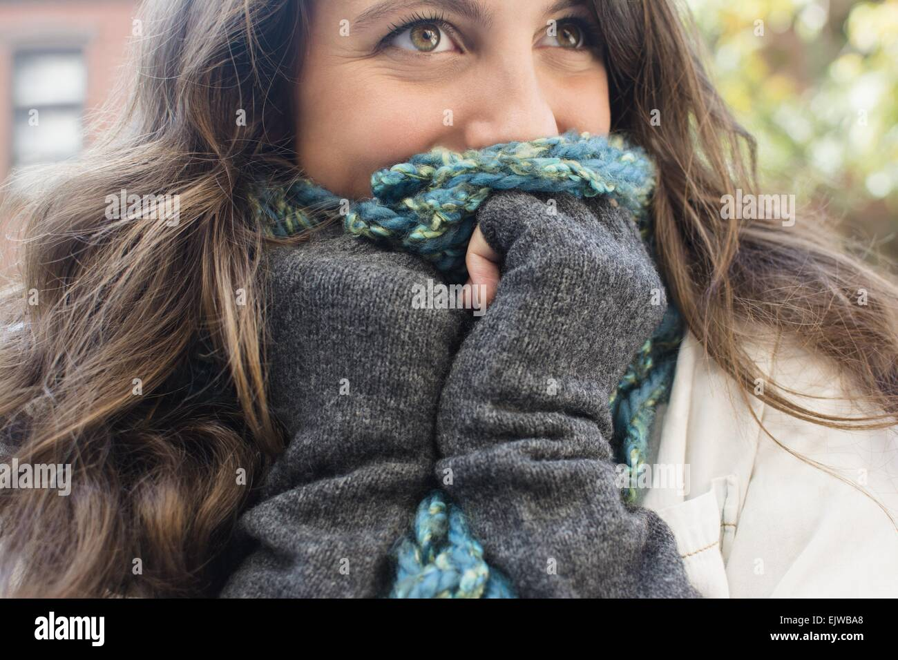 USA, New York State, New York City, Brooklyn, Young woman hiding her face behind scarf - Stock Image