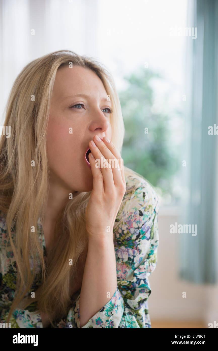 Portrait of woman yawning - Stock Image