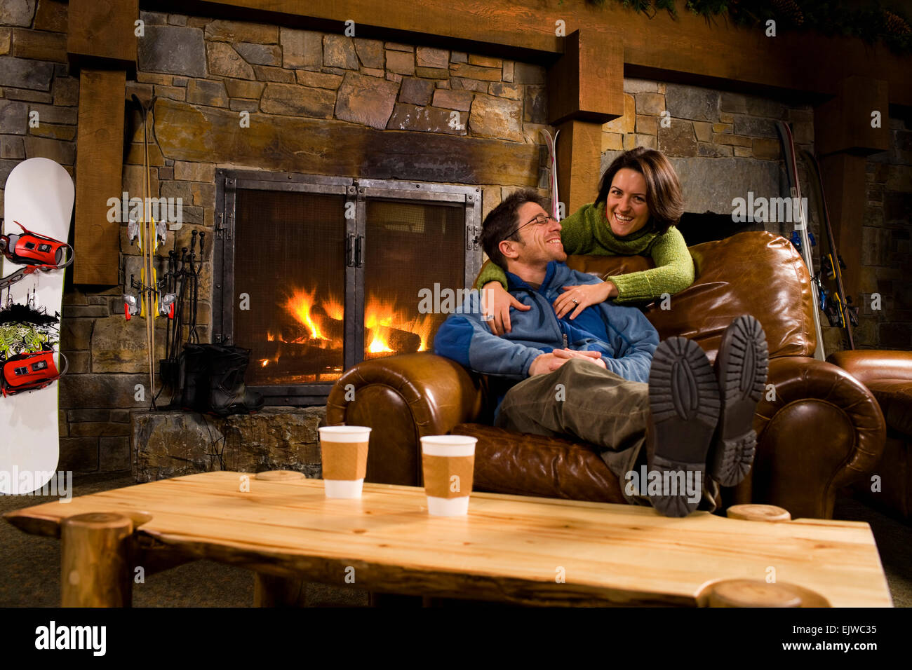 USA, Montana, Whitefish, Man and woman hanging out in front of fireplace - Stock Image