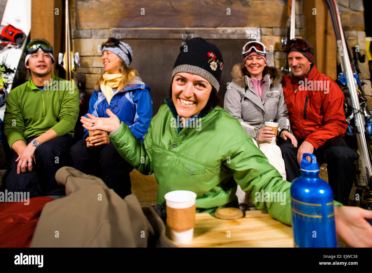 USA, Montana, Whitefish, Group of skiers hanging out at fireplace - Stock Image