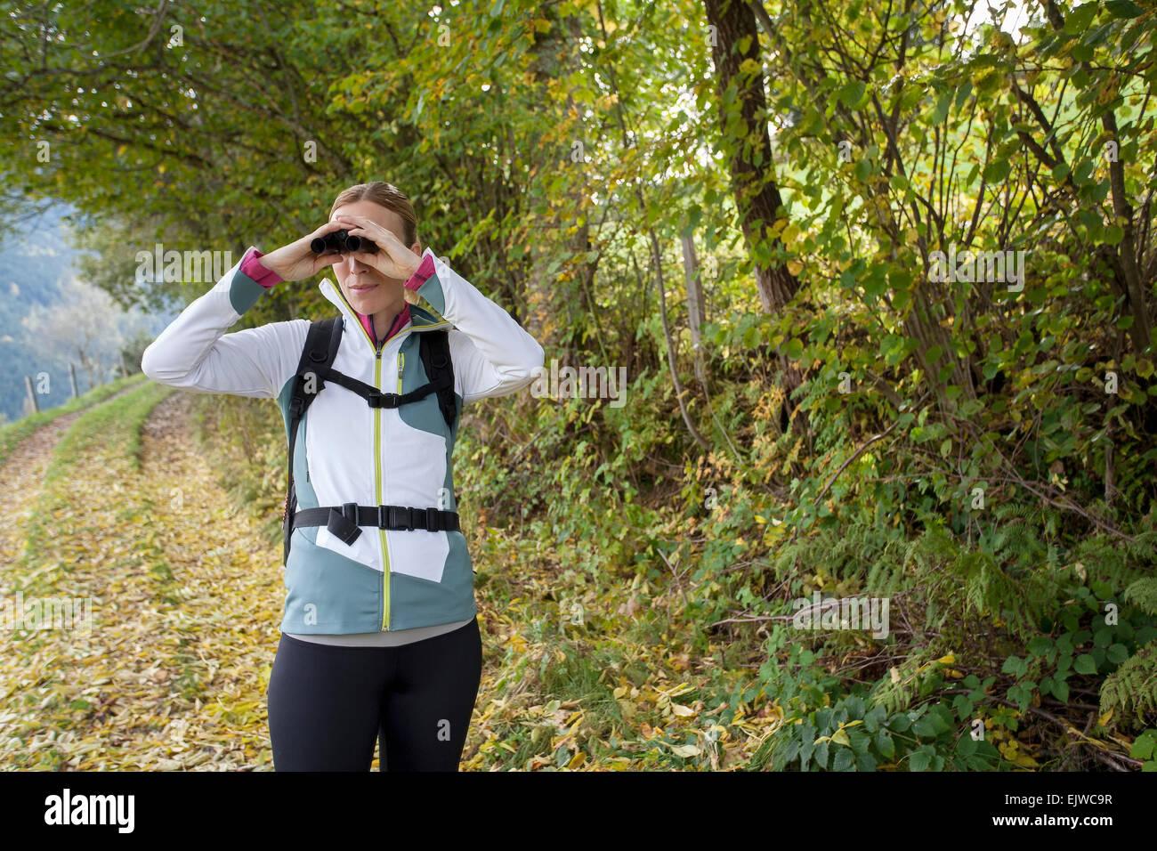 Austria, Salzburger Land, Maria Alm, Woman looking through binoculars - Stock Image