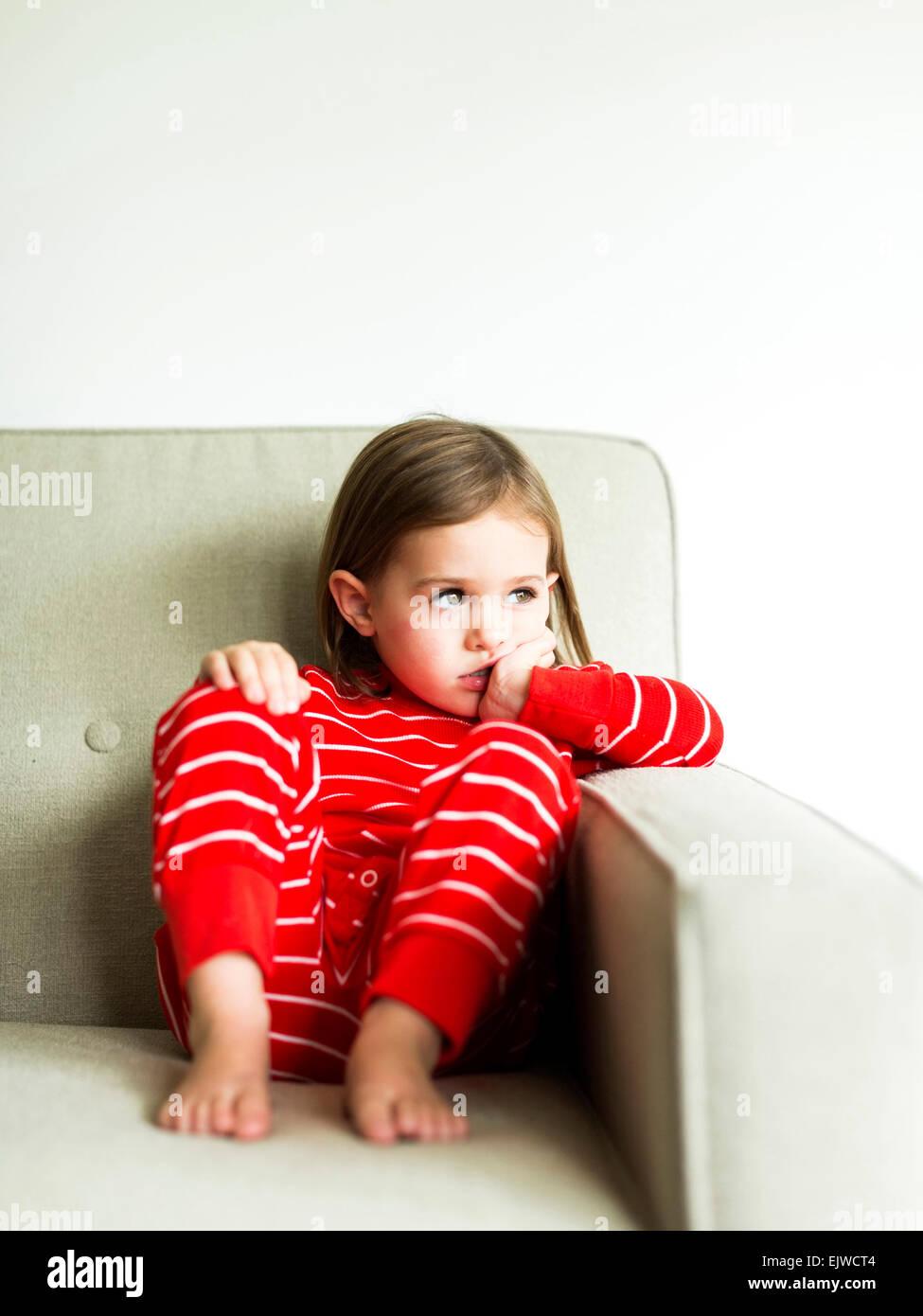 Girl (4-5) in pajamas sitting on sofa - Stock Image