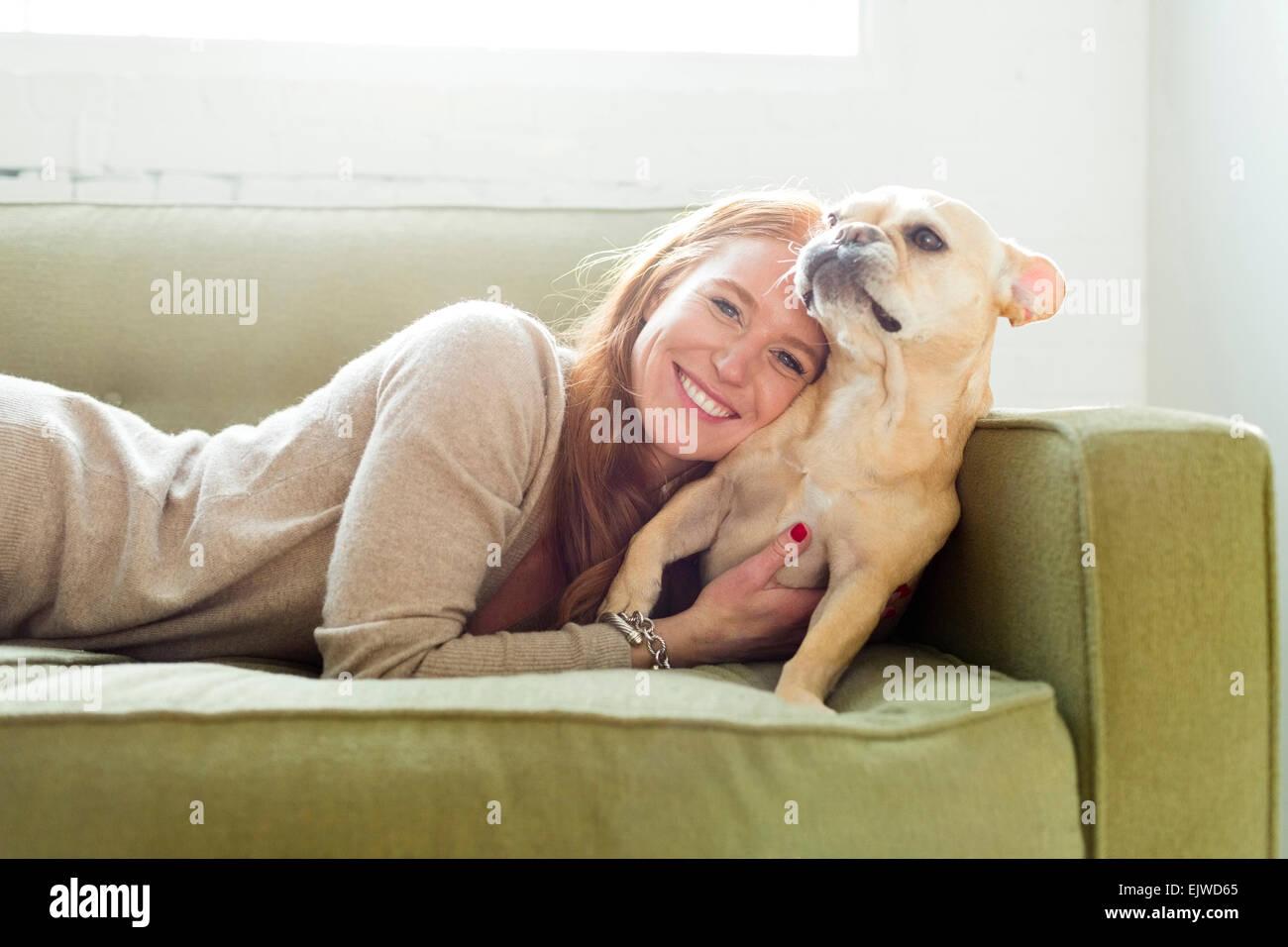 Woman lying on sofa embracing pug - Stock Image
