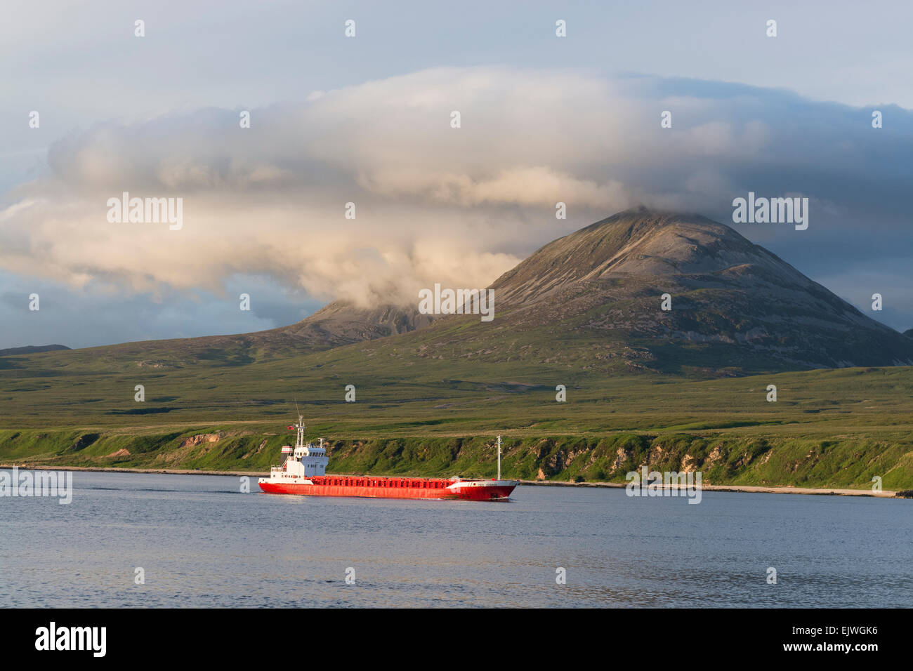 red freighter paps of jura passing port askaig - Stock Image