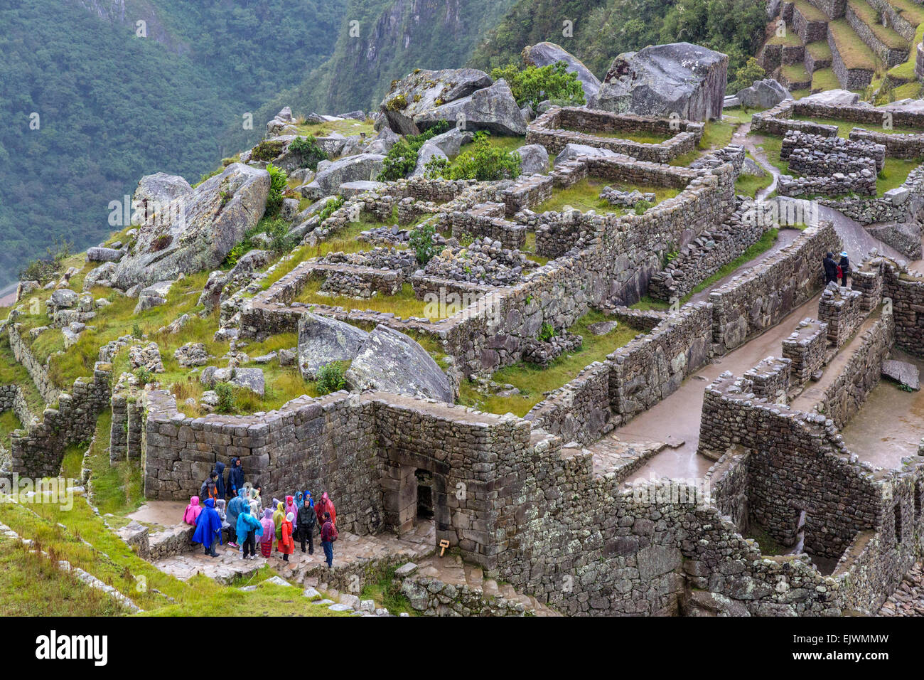 Peru, Machu Picchu.  Early Morning Light Rain Falling.  Tourists in Multicolored Ponchos About to Enter Main Doorway Stock Photo