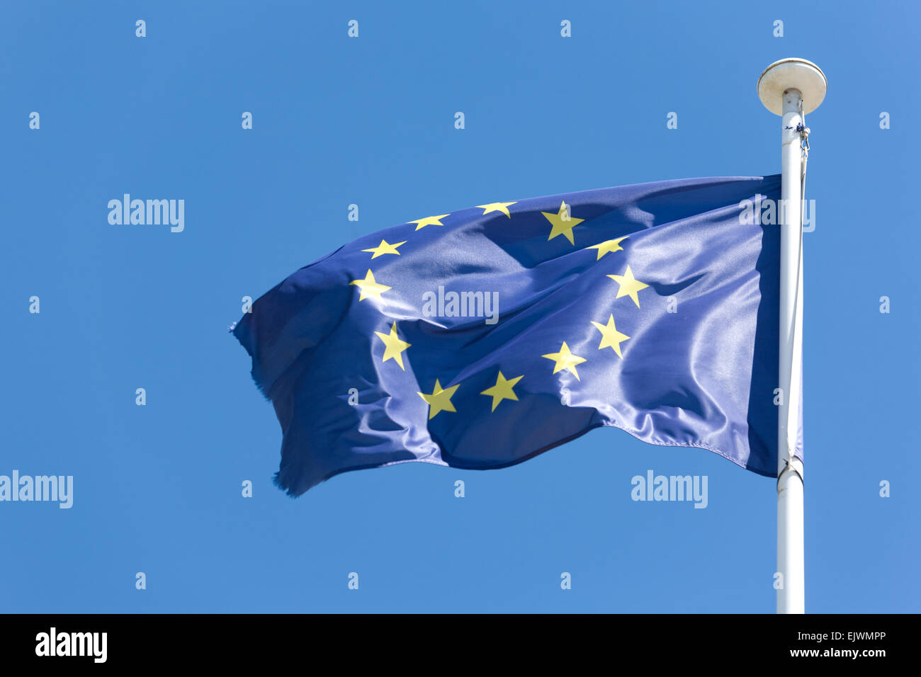 European Union flag fluttering in a brisk breeze against a blue sky - Stock Image