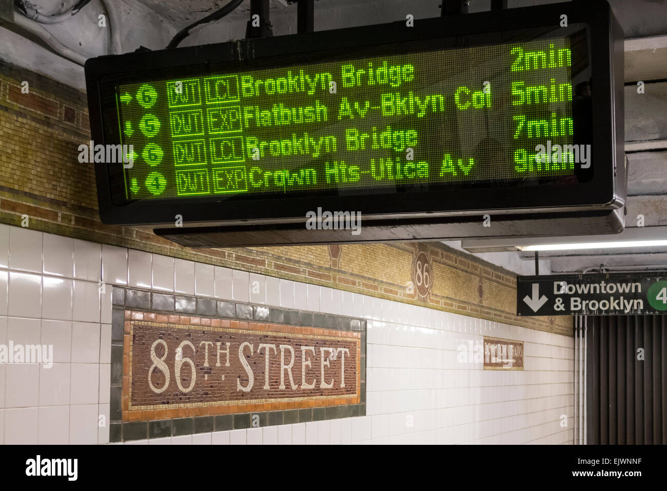 Subway train arrivals schedule shown on a digital readout at East 86th Street station - Stock Image