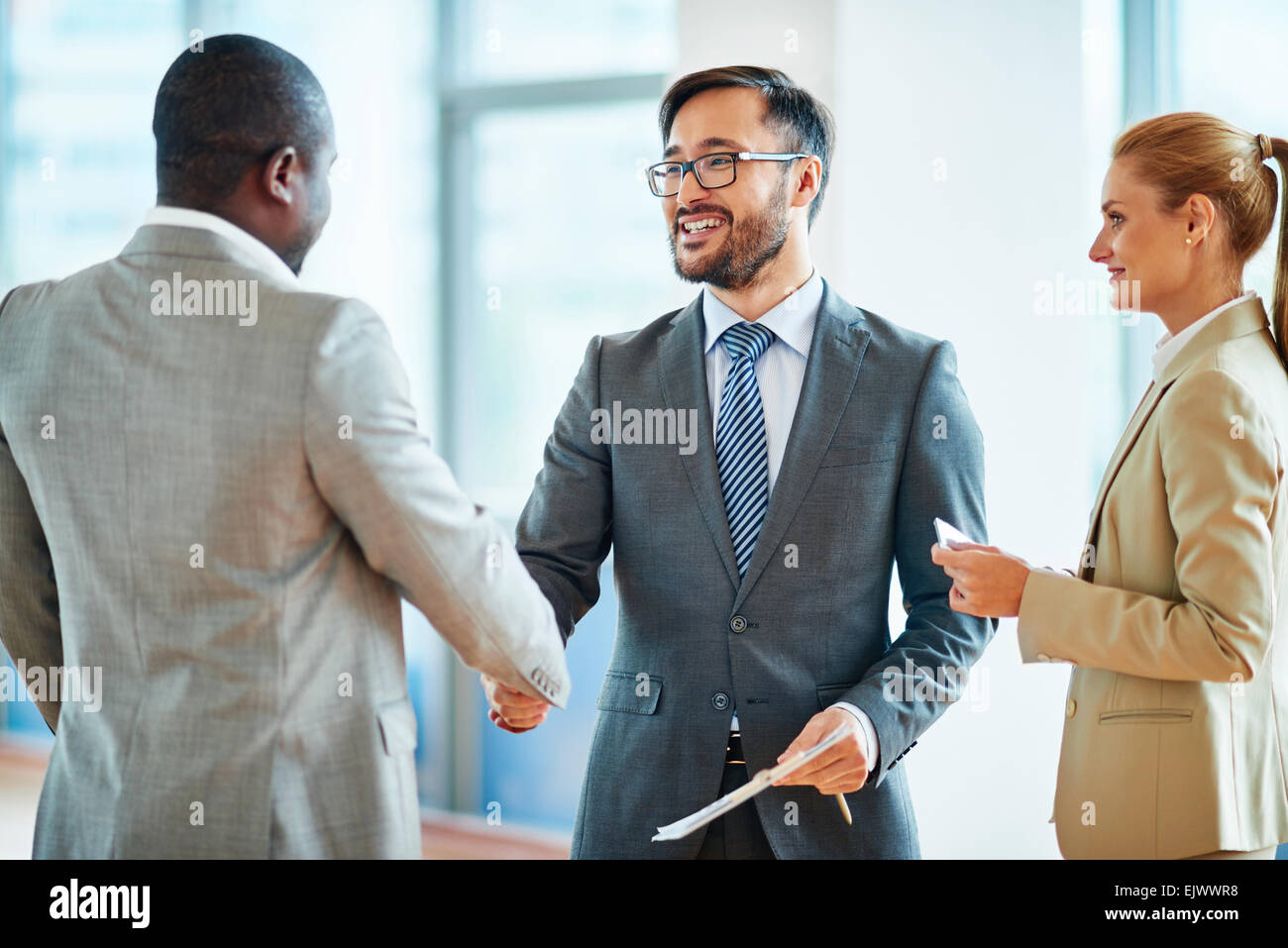 Happy businessmen handshaking after striking deal - Stock Image