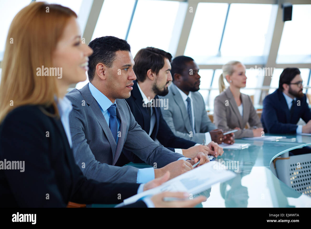 Row of serious business people attending seminar - Stock Image