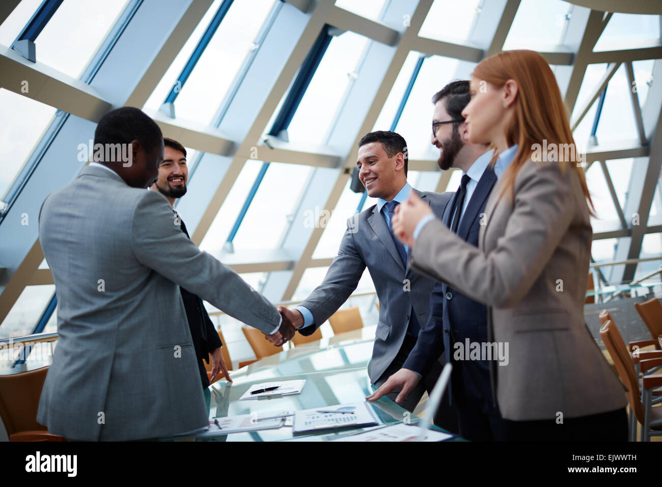 Business partners handshaking upon striking deal in office - Stock Image