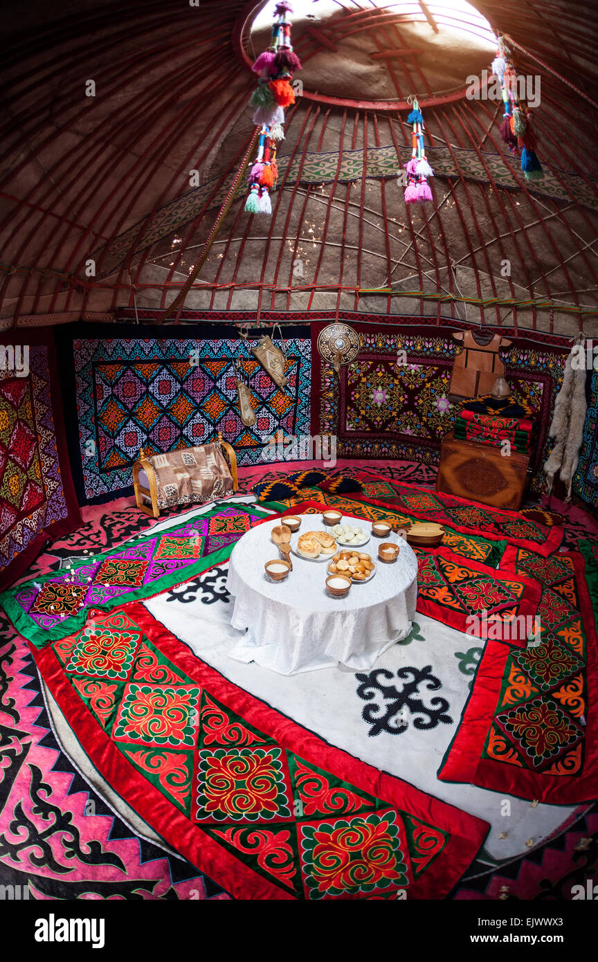 Ethnic nomadic house yurt interior with table of national food at Nauryz celebration - Stock Image