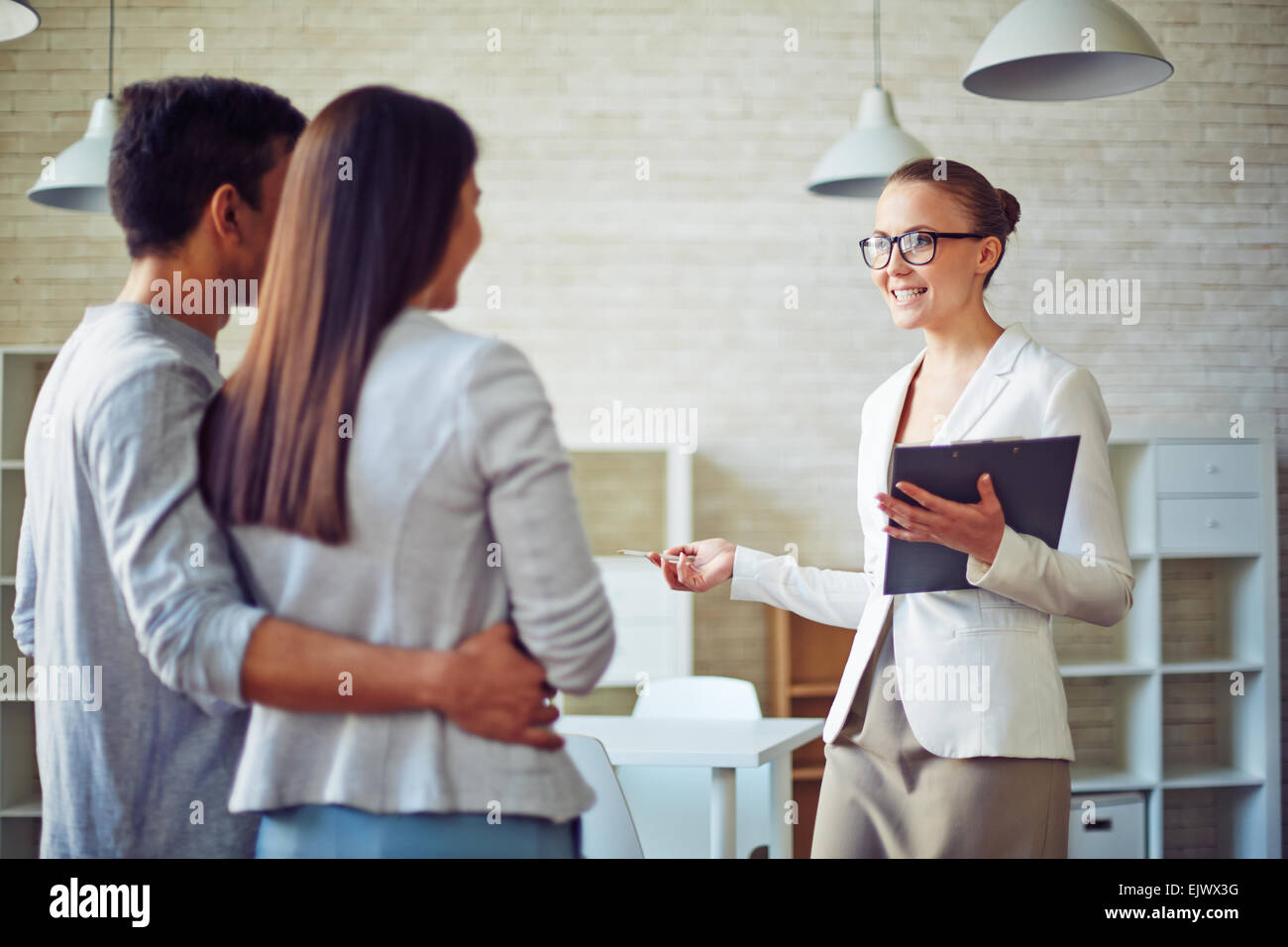 Female broker consulting young couple in realtor office - Stock Image