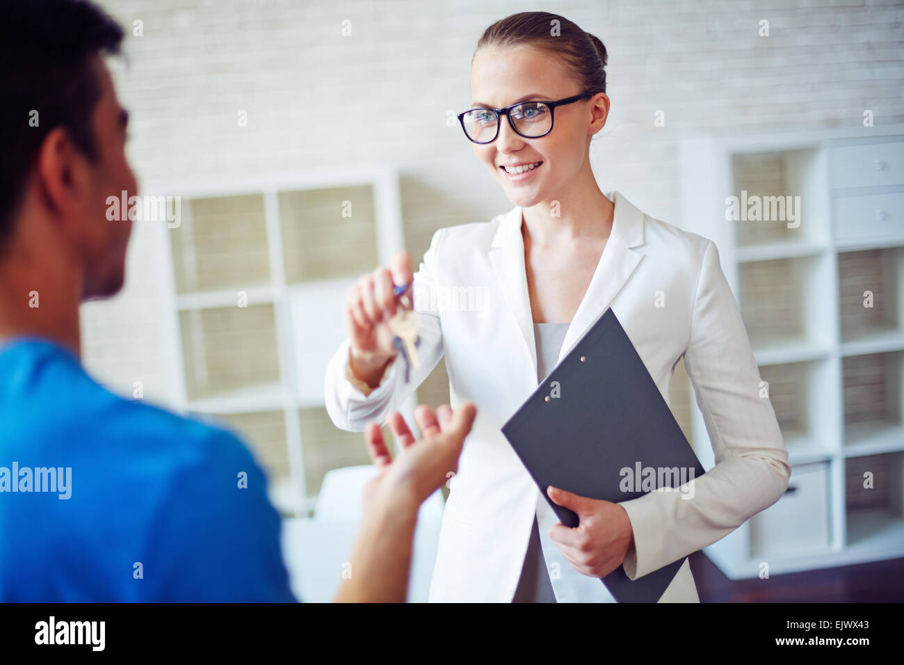 Real estate specialist giving her client key from new residence - Stock Image