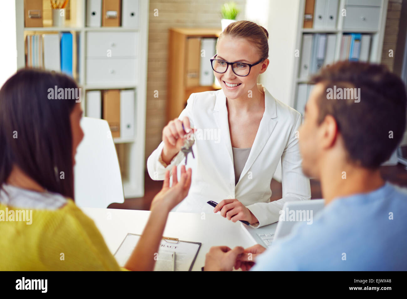 Female realtor giving young couple key from real estate - Stock Image