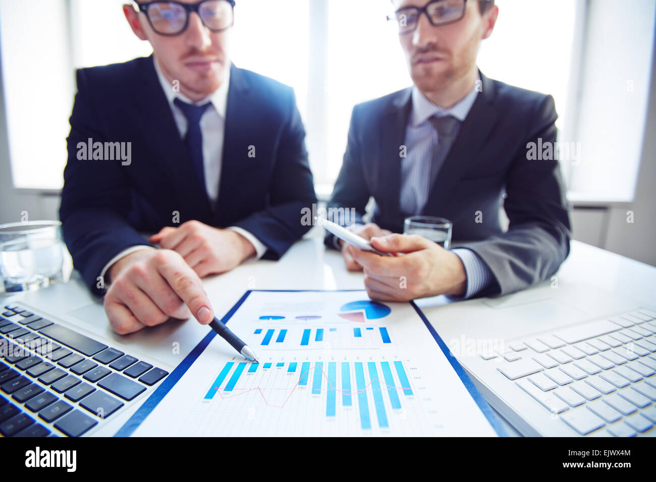 Close-up of businessmen analyzing chart at meeting - Stock Image