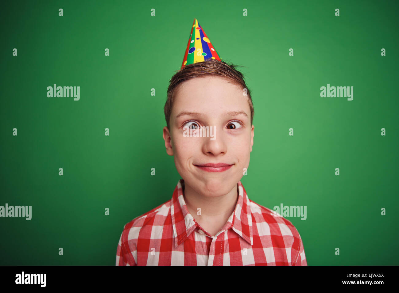 Cute boy grimacing at fool's day celebration - Stock Image