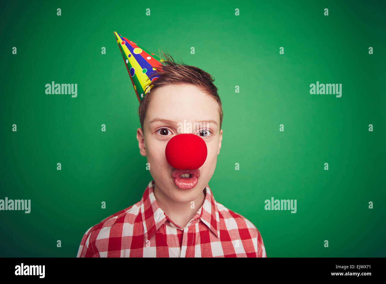 Cute boy with red clown nose grimacing - Stock Image