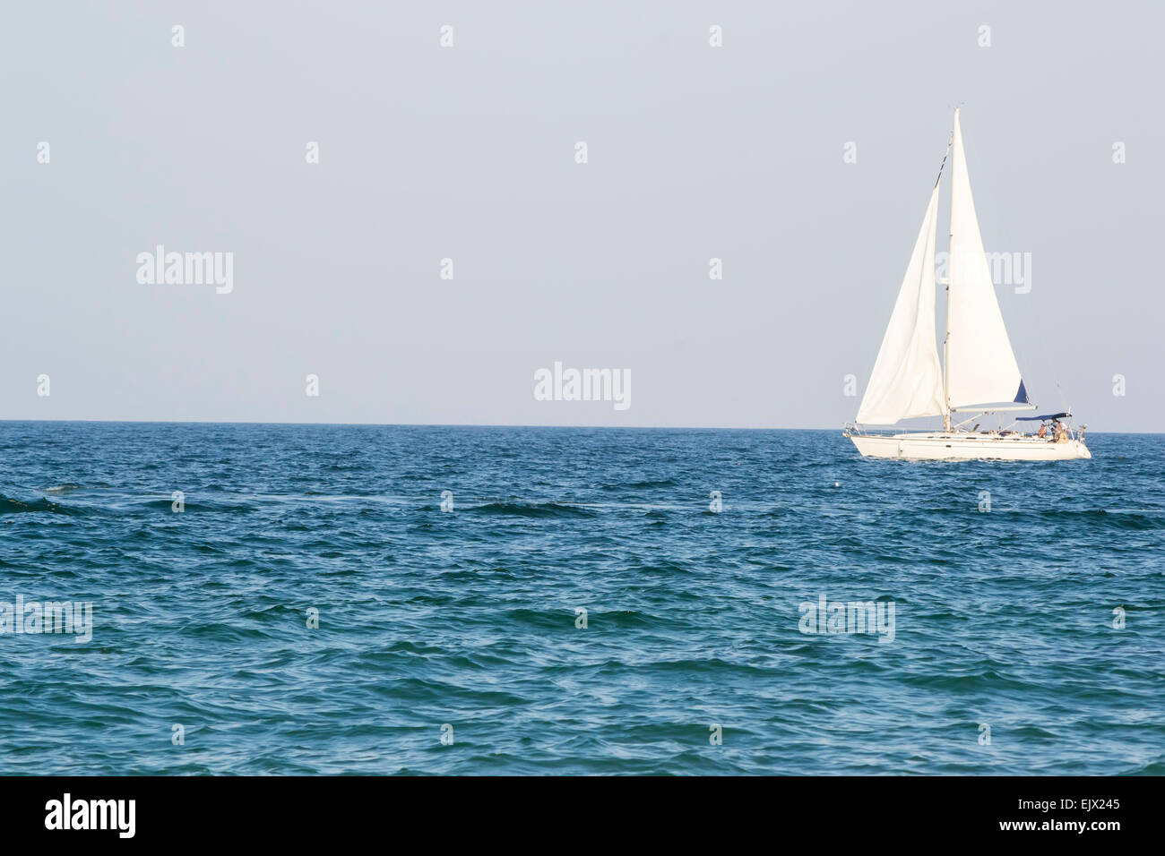 Sail boat navigating towards east on calm blue sea - Stock Image