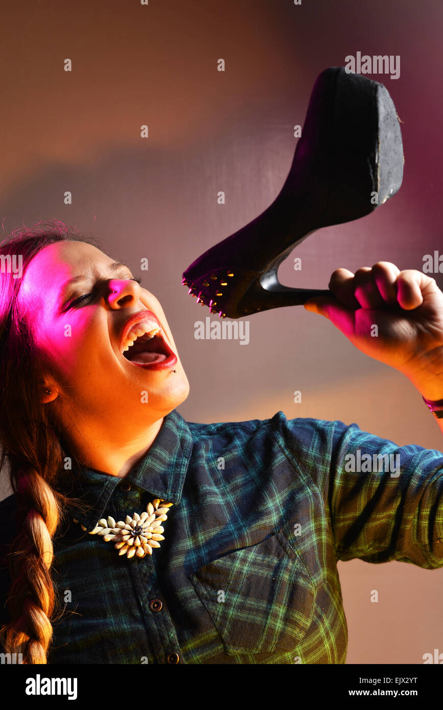 Kerrianne Covell, a former X Factor contestant pretending to use a shoe as a microphone. She previously worked in - Stock Image