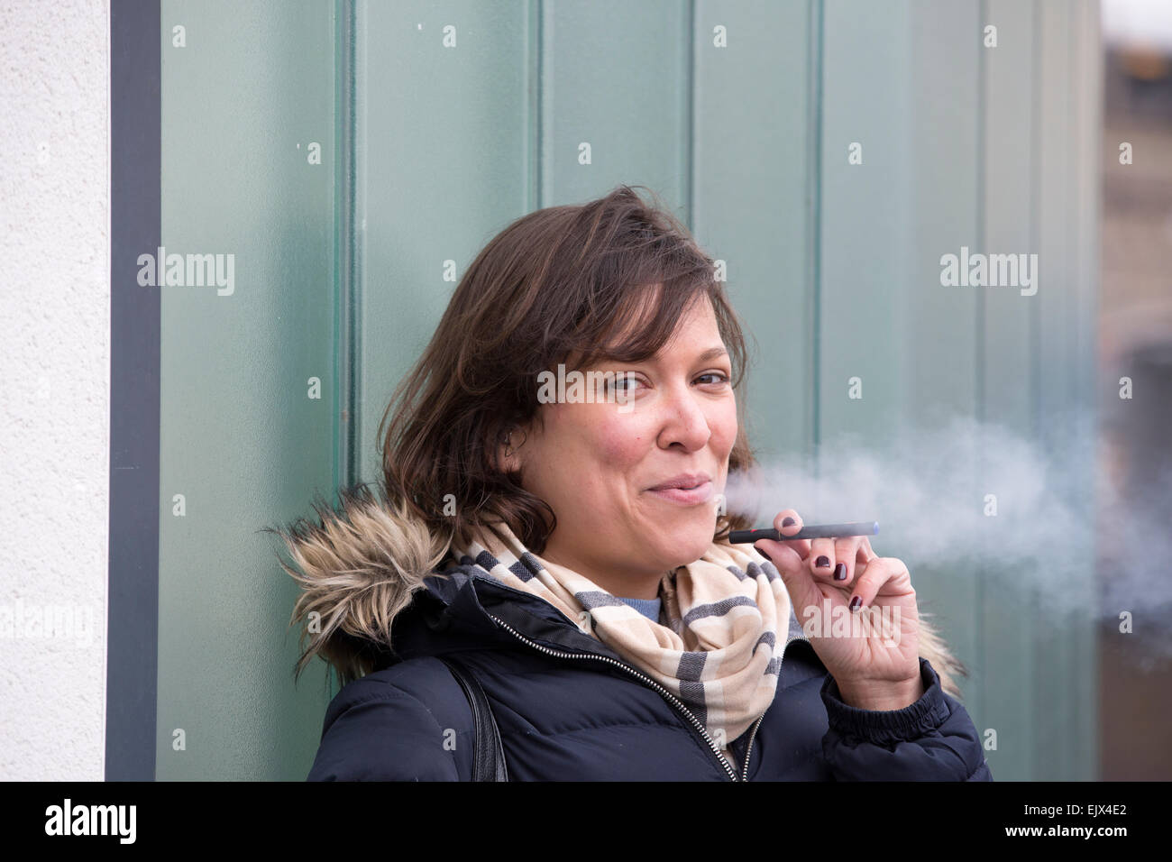Woman smoking an e-cigarette outside an office building, UK - Stock Image