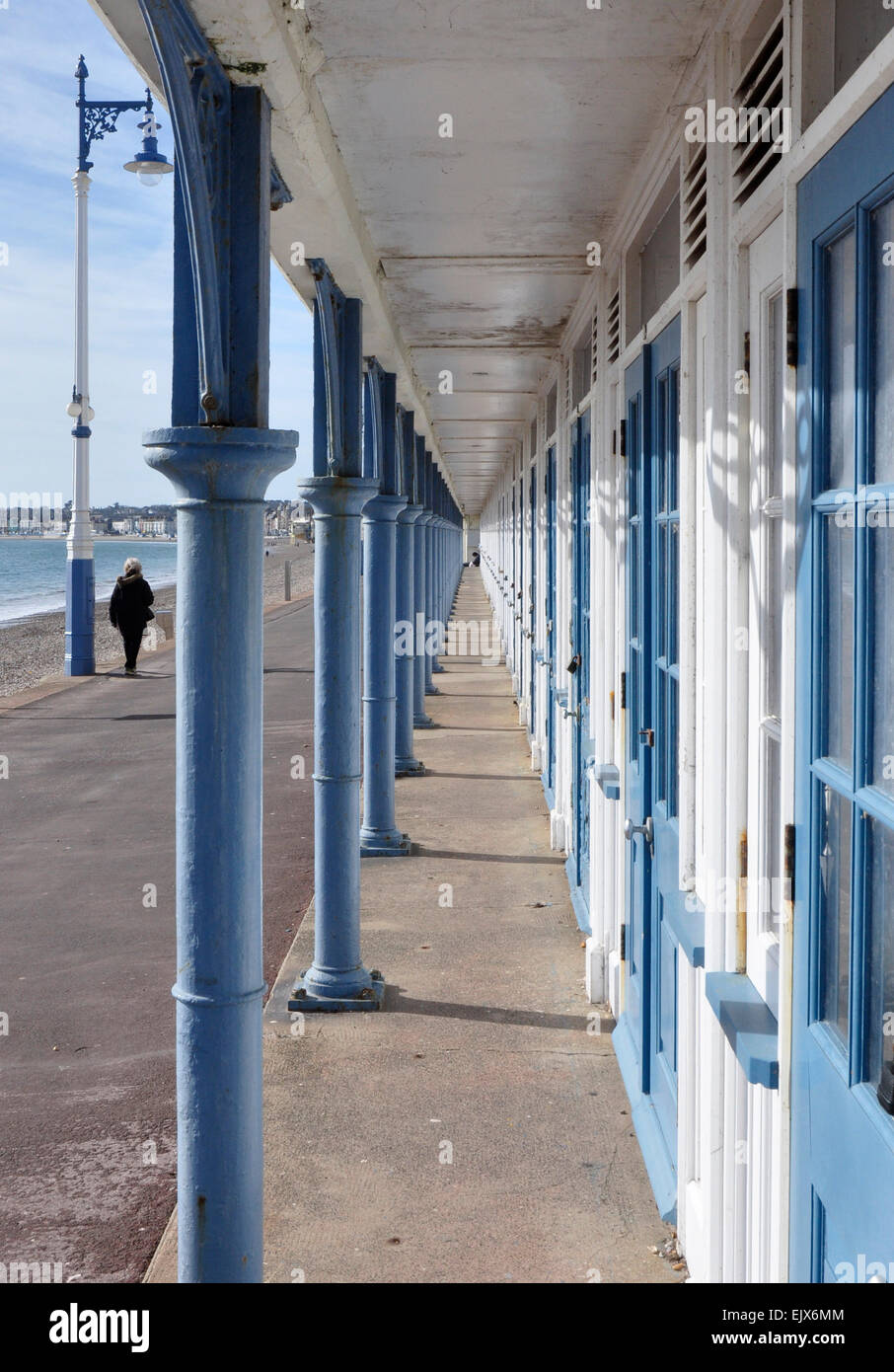 Deserted seaside promenade - solitary woman walking away - parallel with arched arcade - dramatic view to vanishing - Stock Image