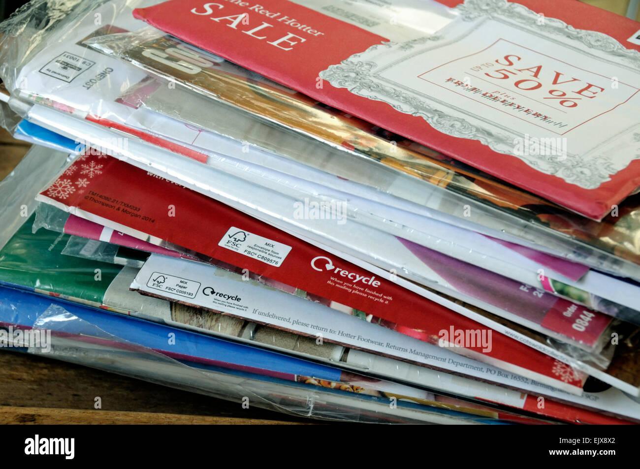 Pile of unopened envelopes containing clothing catalogues London, UK - Stock Image
