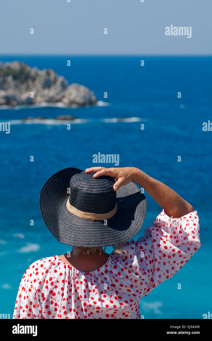 Rear view of a woman overlooking the sea - Stock Image