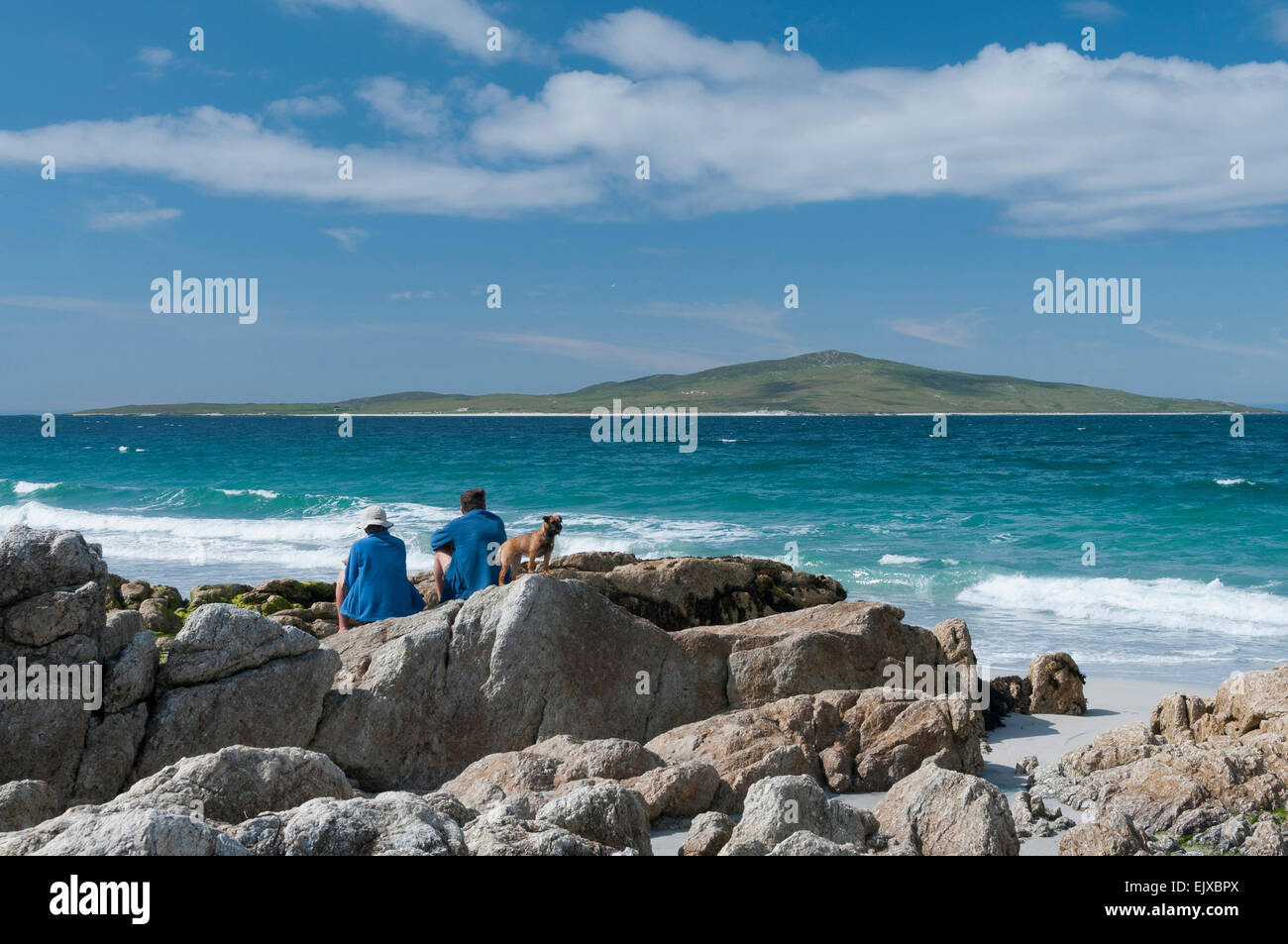 waves crashing at pabbay view with walkers / tourist relaxing with border terrier - Stock Image