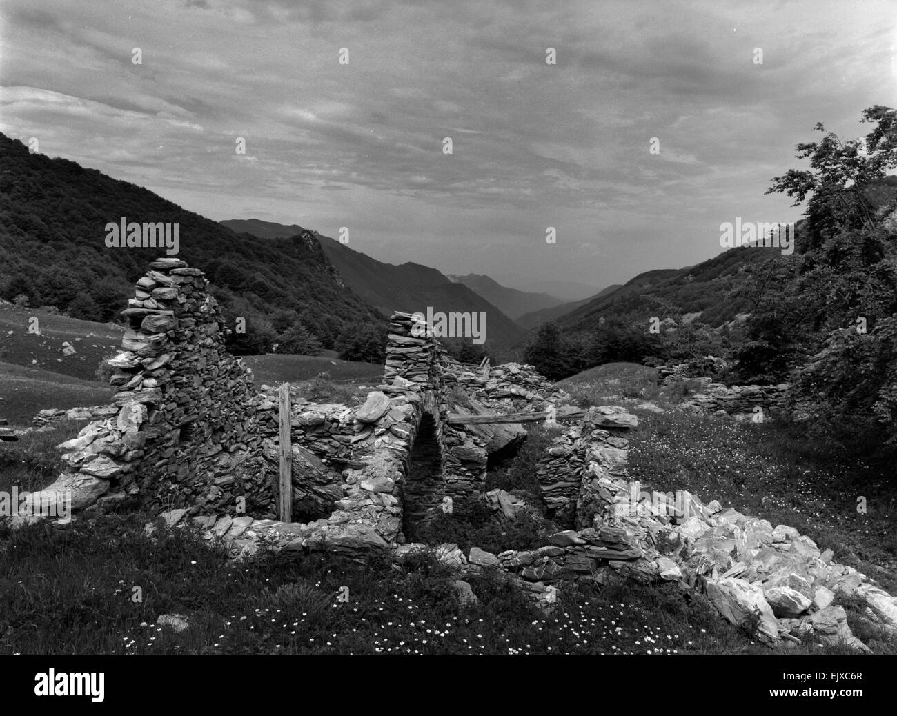 Black and white landscape of ruins in the foreground and mountains in the background under heavy sky. - Stock Image