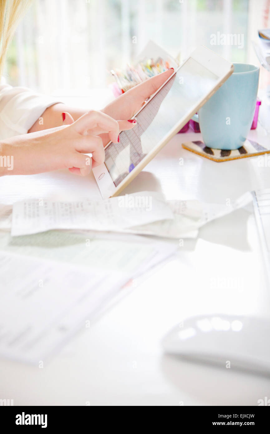 Woman Using Tablet Computer whilst Sorting Out Bills, Close-up View Stock Photo