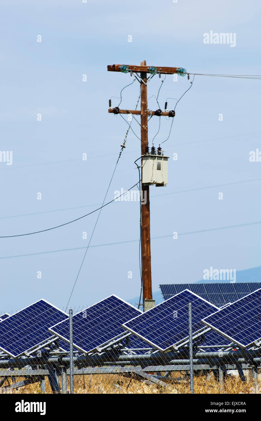 Solar power modules and electricity pylon in Thessaly, Greece - Stock Image