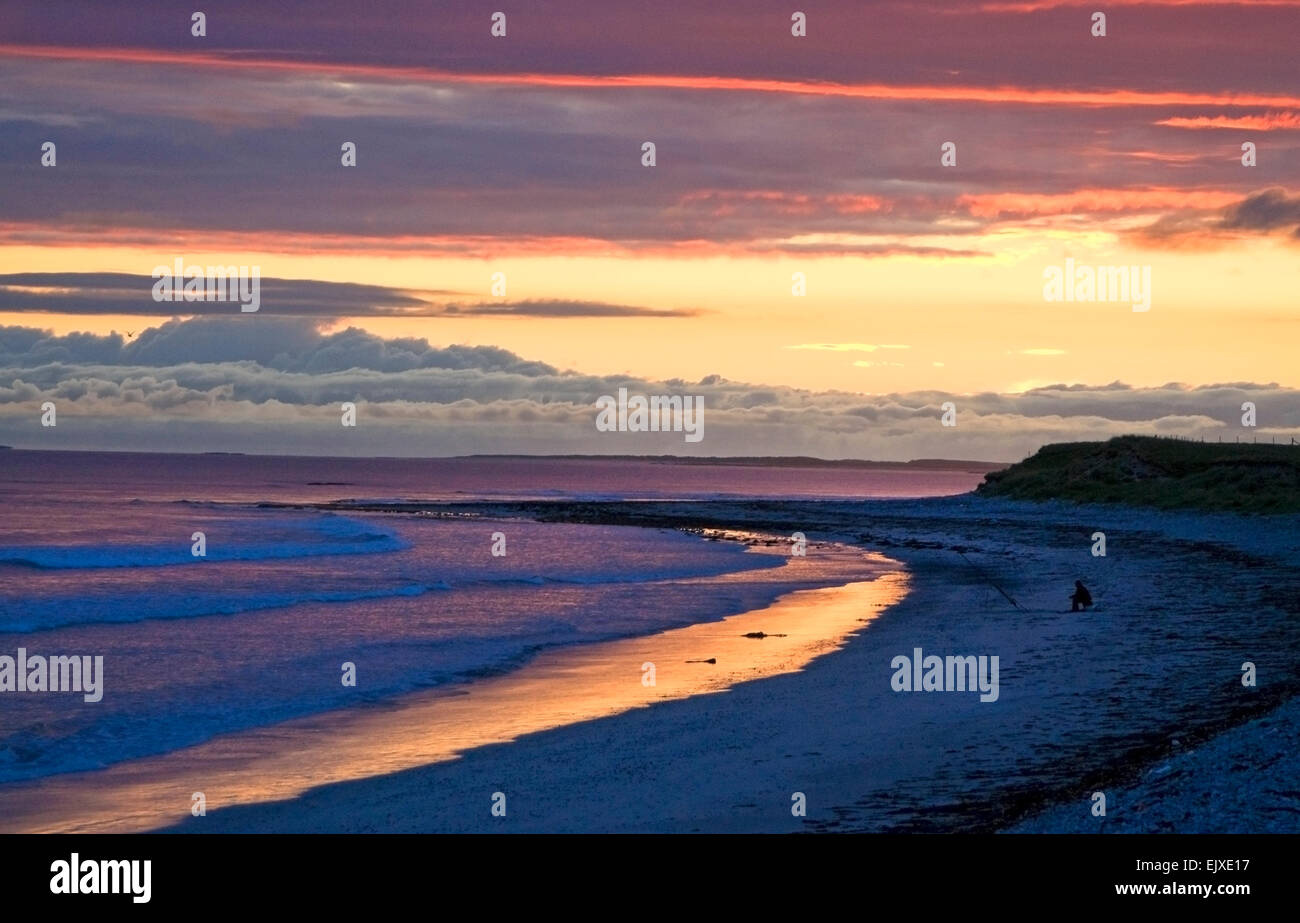 sunset at baleshare north uist  with lone fisherman - Stock Image