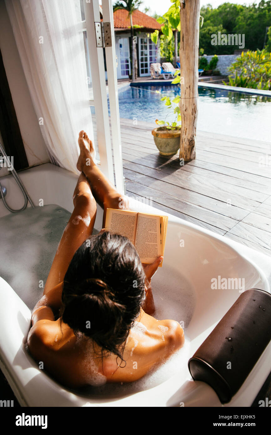 Woman relaxing in bathtub reading book Stock Photo: 80489897 - Alamy