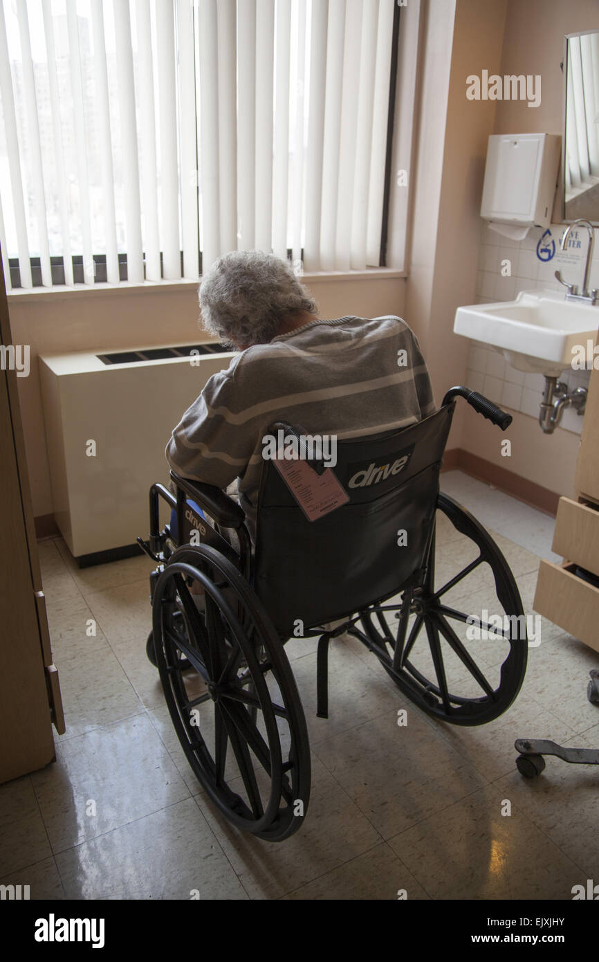 Man with vascular dementia sits alone in a nursing home in