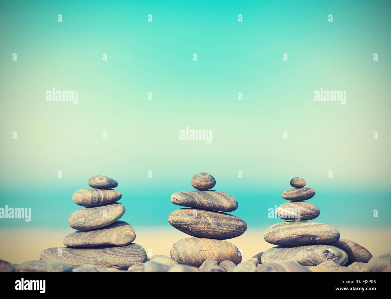 Vintage retro style image of stone pyramids on beach, Zen spa concept background. - Stock Image