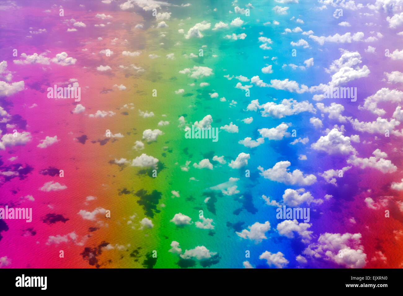 Rainbow colors over the ocean surface with clouds above Stock Photo