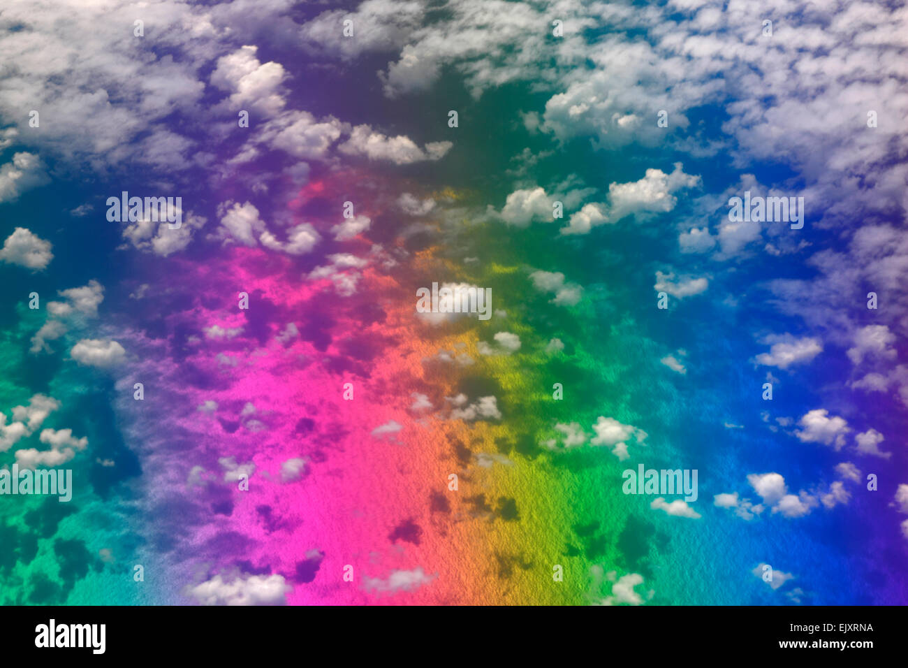 Rainbow colors over the ocean surface with clouds above - Stock Image