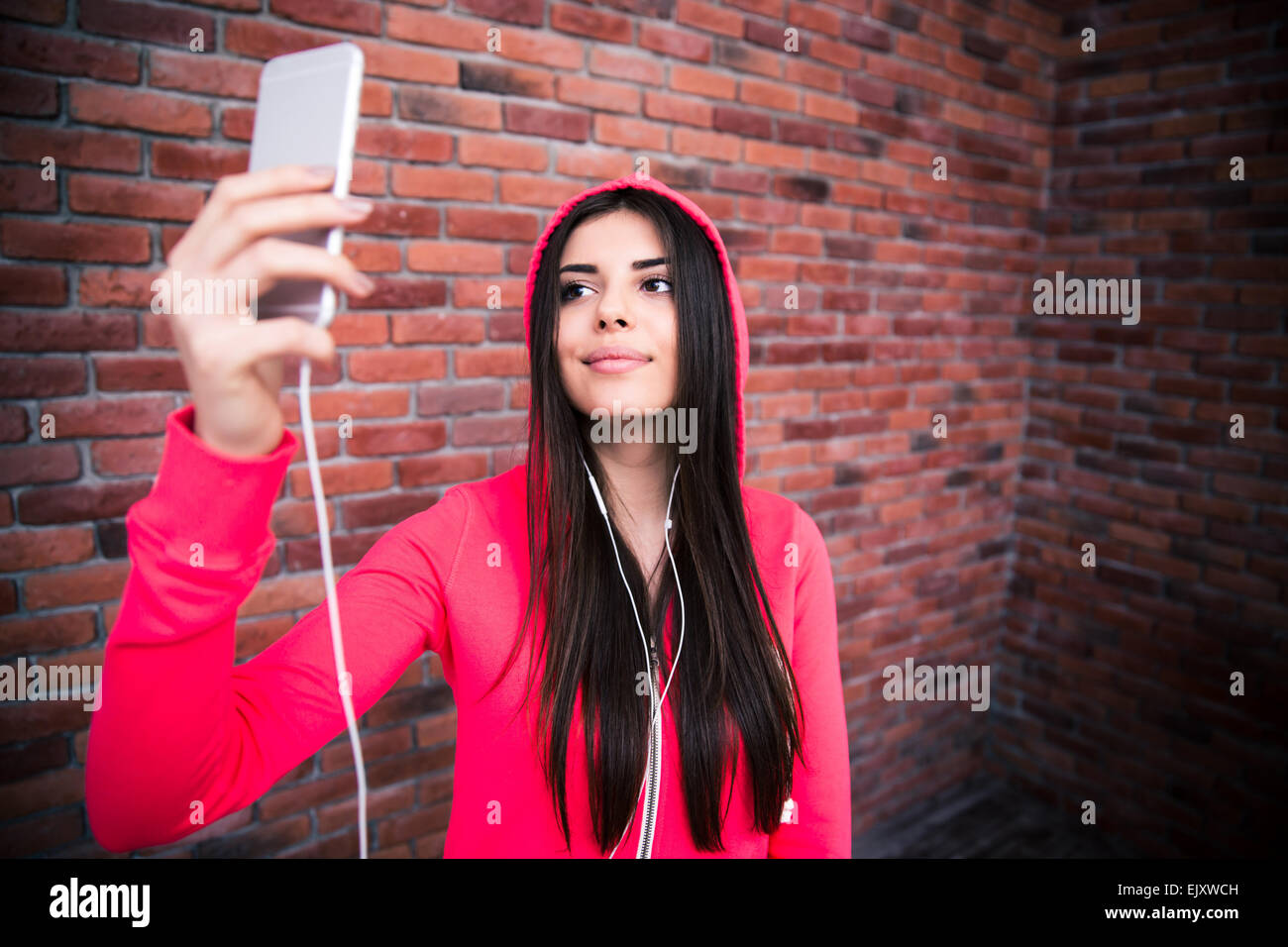 Happy young sportive woman making selfie photo with smartphone over brick wall - Stock Image