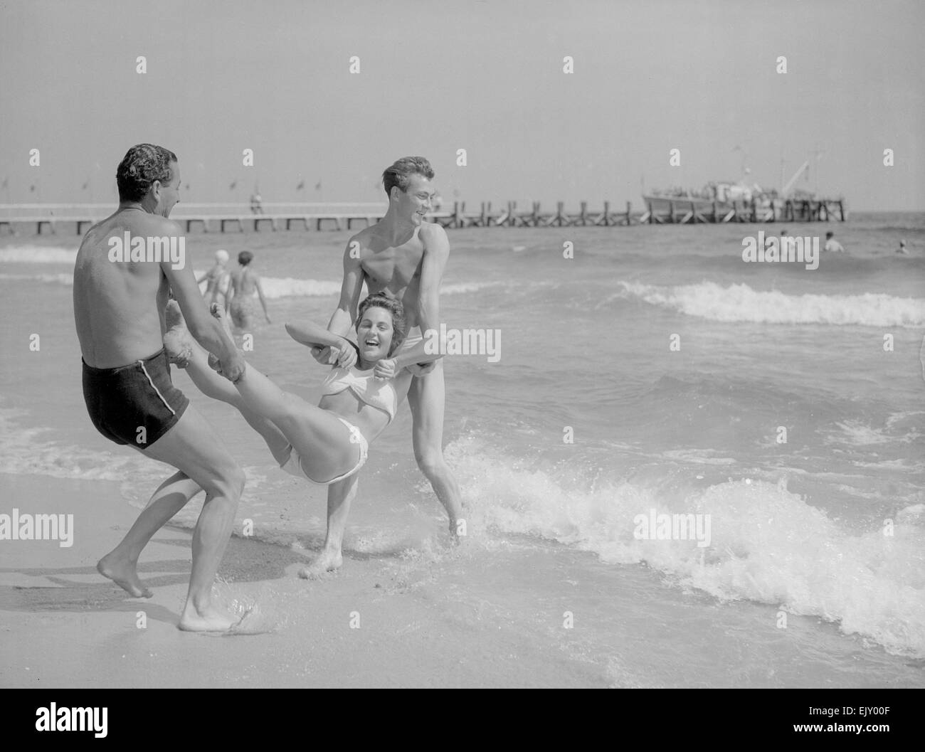 Two men throwing a young woman into the sea on Bournemouth beach. 10th Aust 1952 Stock Photo